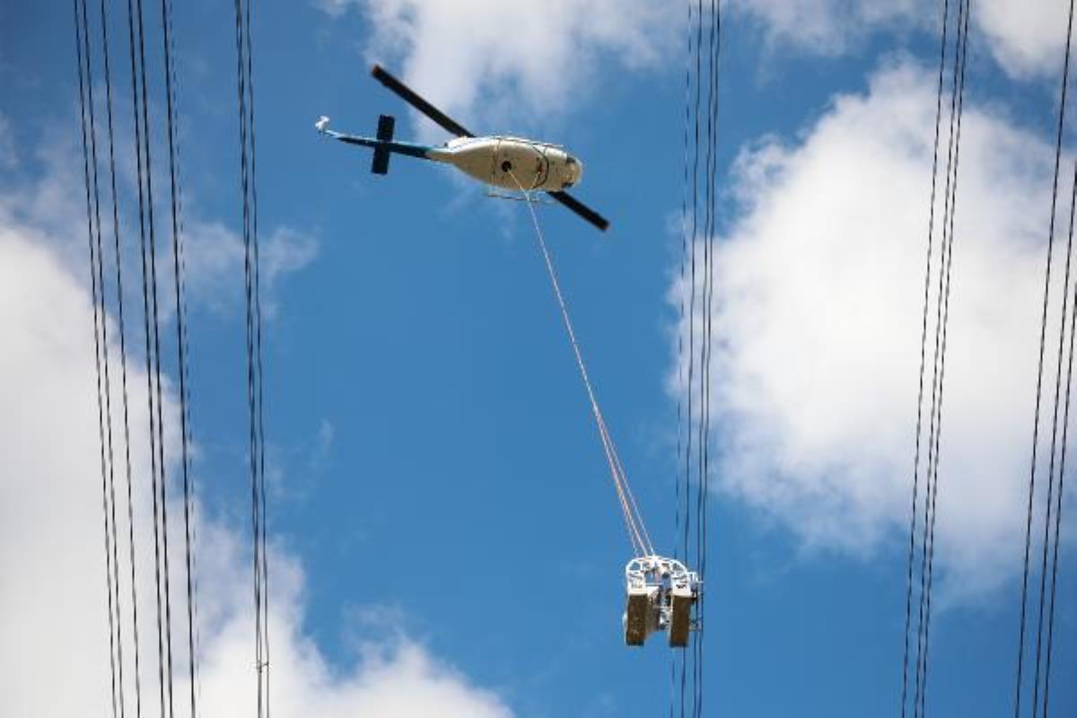 Helikoptere bağlı sepetle elektrik iletim hatlarına bakım yaparken ölüme meydan okuyorlar