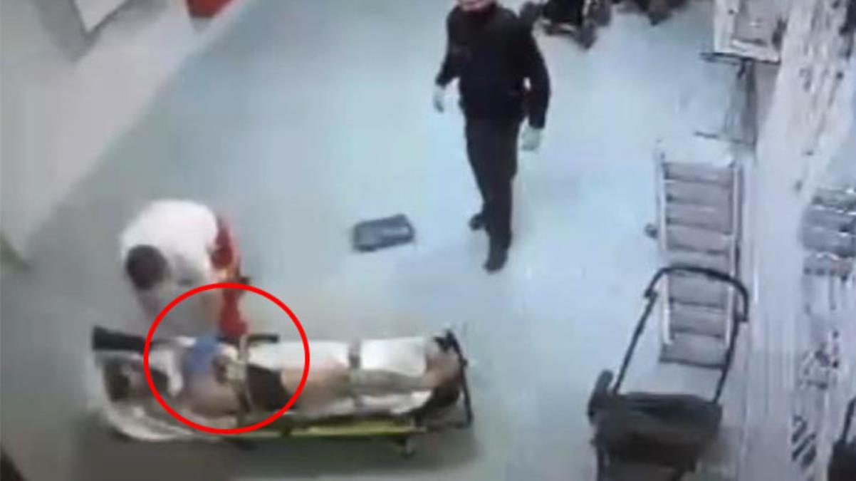 Elleri bağlı sedyede yatan göçmen, ambulans şoförü tarafından darp edildi